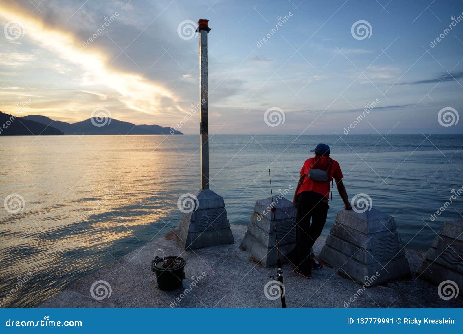 Ψαράς που παίρνει ένα σπάσιμο σε Batu Ferringhi