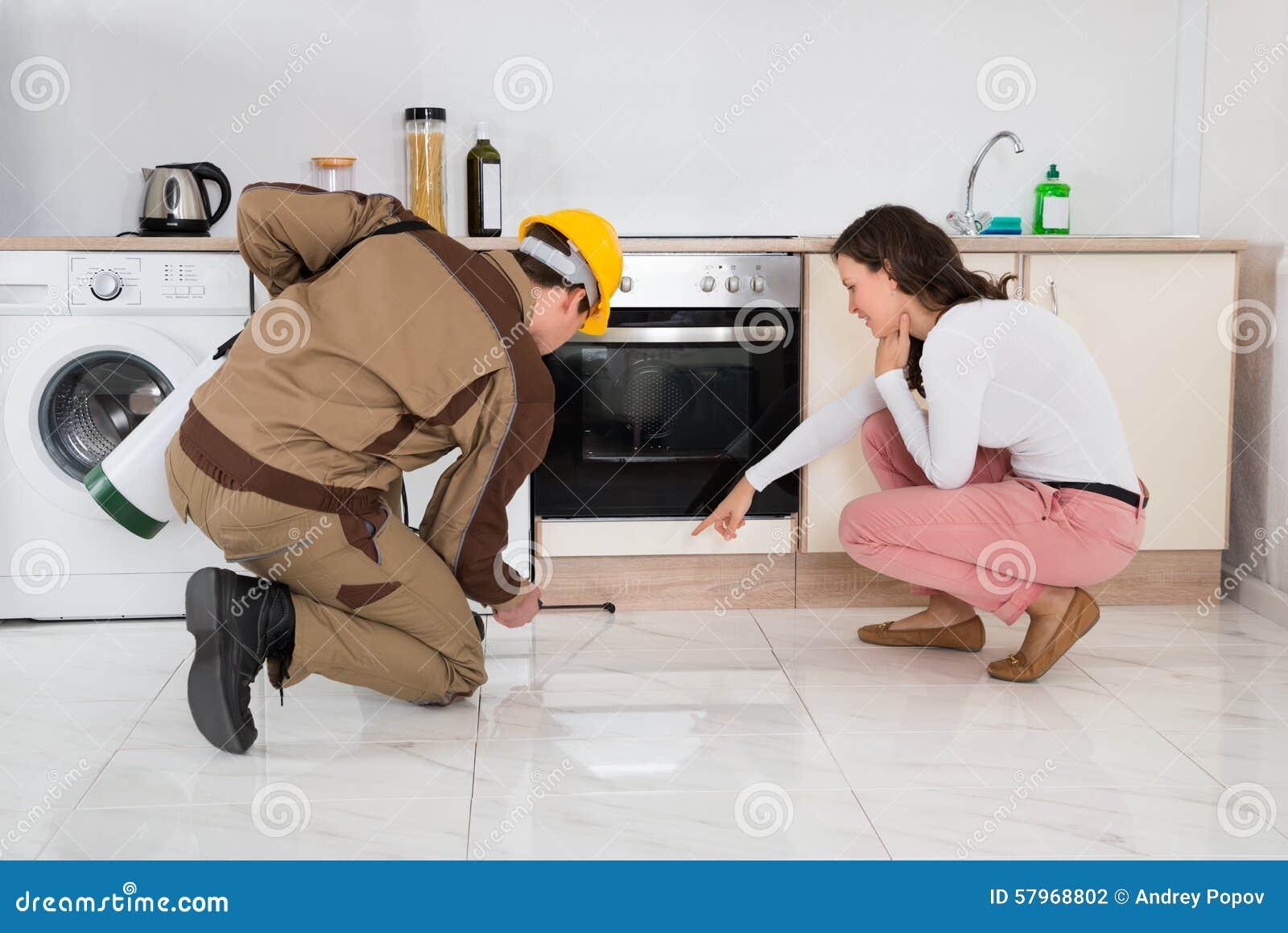 Ψεκάζοντας εντομοκτόνα εργαζομένων μπροστά από τη νοικοκυρά