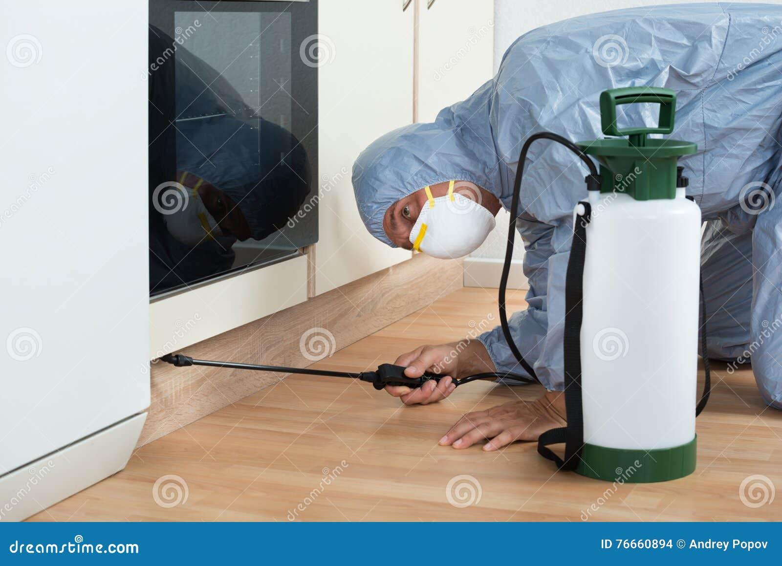 Ψεκάζοντας φυτοφάρμακο εξολοθρευτών στο ξύλινο γραφείο