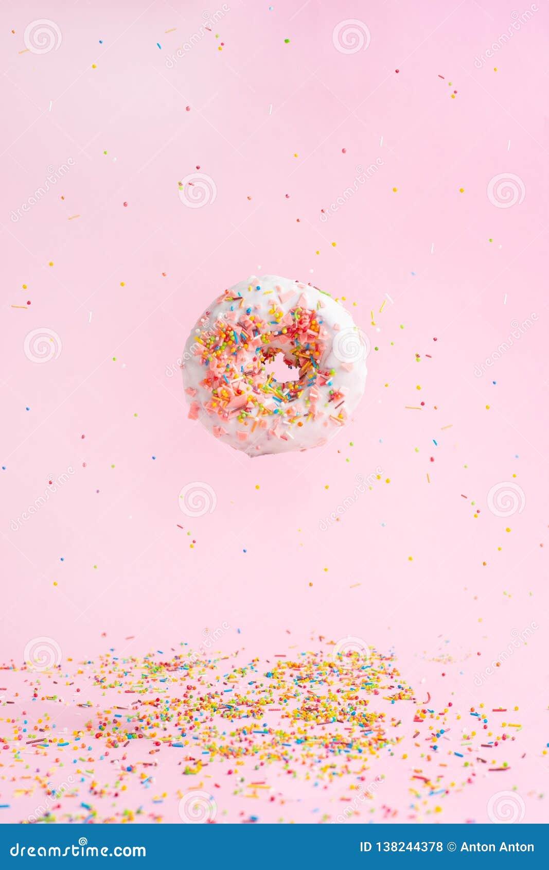 Ψεκάστε ρόδινο doughnut Πολύχρωμος ψεκάστε doughnut σε ένα ρόδινο υπόβαθρο Παγετός στον αέρα