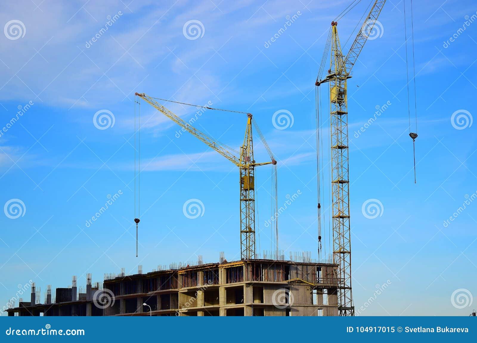 Ψηλή στάση γερανών δύο κοντά σε ένα σπίτι κάτω από την κατασκευή στο υπόβαθρο μπλε ουρανού