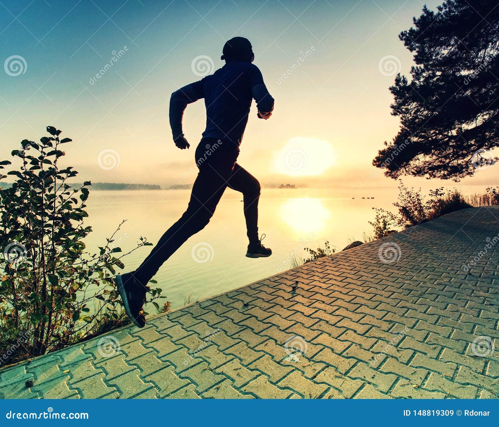 Ψηλός τρέχοντας αθλητικός τύπος που φορά τα καθιερώνοντα τη μόδα τρέχοντας παπούτσια και αθλητικά τα ενδύματα