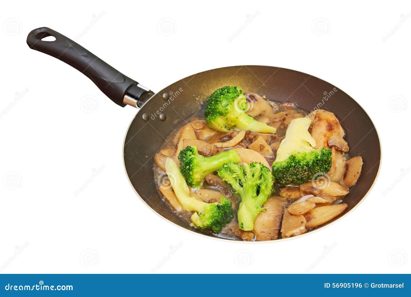 Ψημένα μανιτάρια και μπρόκολο στο τηγάνισμα του τηγανιού απομονωμένος