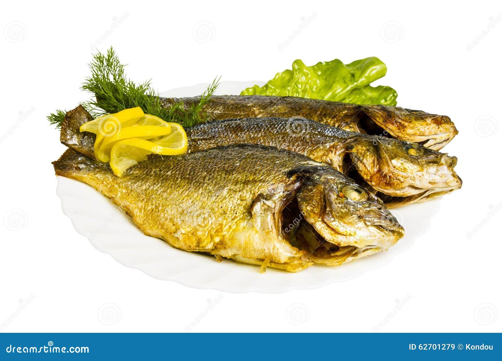 Ψημένα στη σχάρα ψάρια με τα πράσινα στο πιάτο, που απομονώνονται