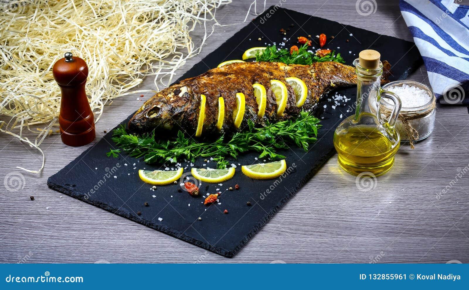 Ψημένα στη σχάρα ψάρια ποταμών σε ένα πιάτο με το λεμόνι και τα ψημένους λαχανικά και το μαϊντανό Φωτογραφία συνταγής τροφίμων, κ