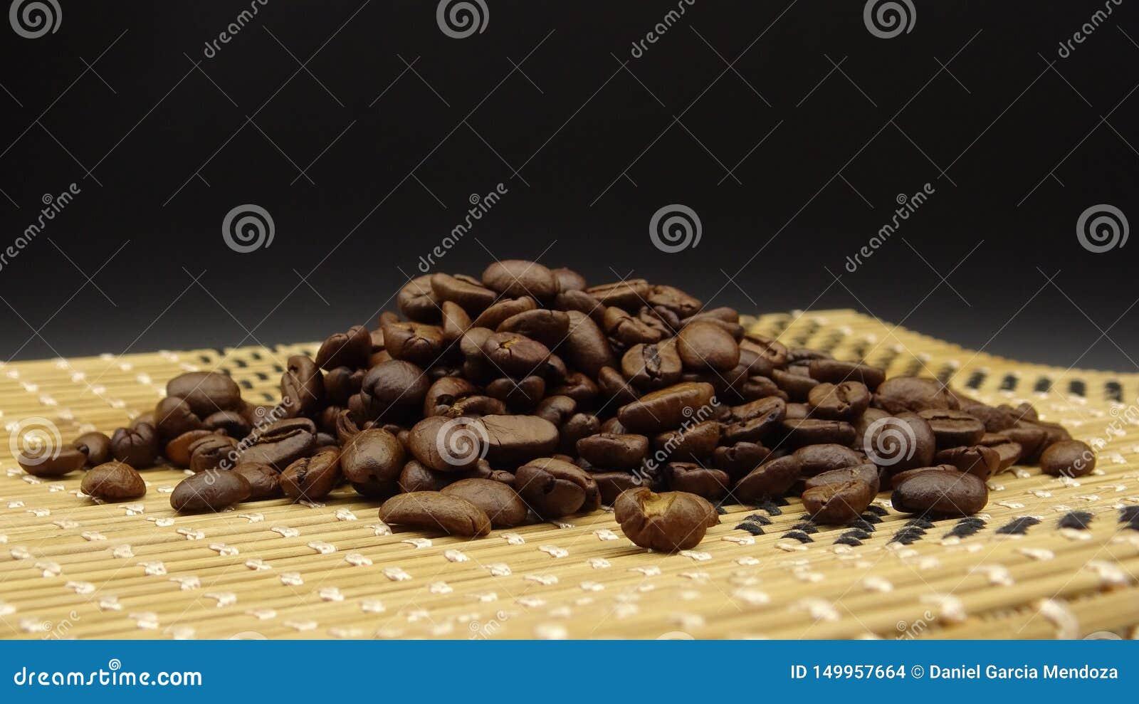 Ψημένα φασόλια καφέ πέρα από το ξύλο στο μαύρο υπόβαθρο