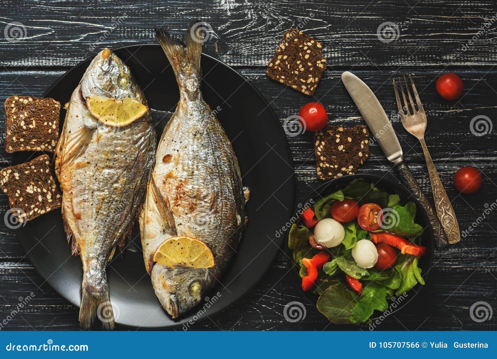 Ψημένα ψάρια Dorado σε ένα μαύρο πιάτο, σαλάτα με τη μοτσαρέλα ντοματών και φύλλα μαρουλιού