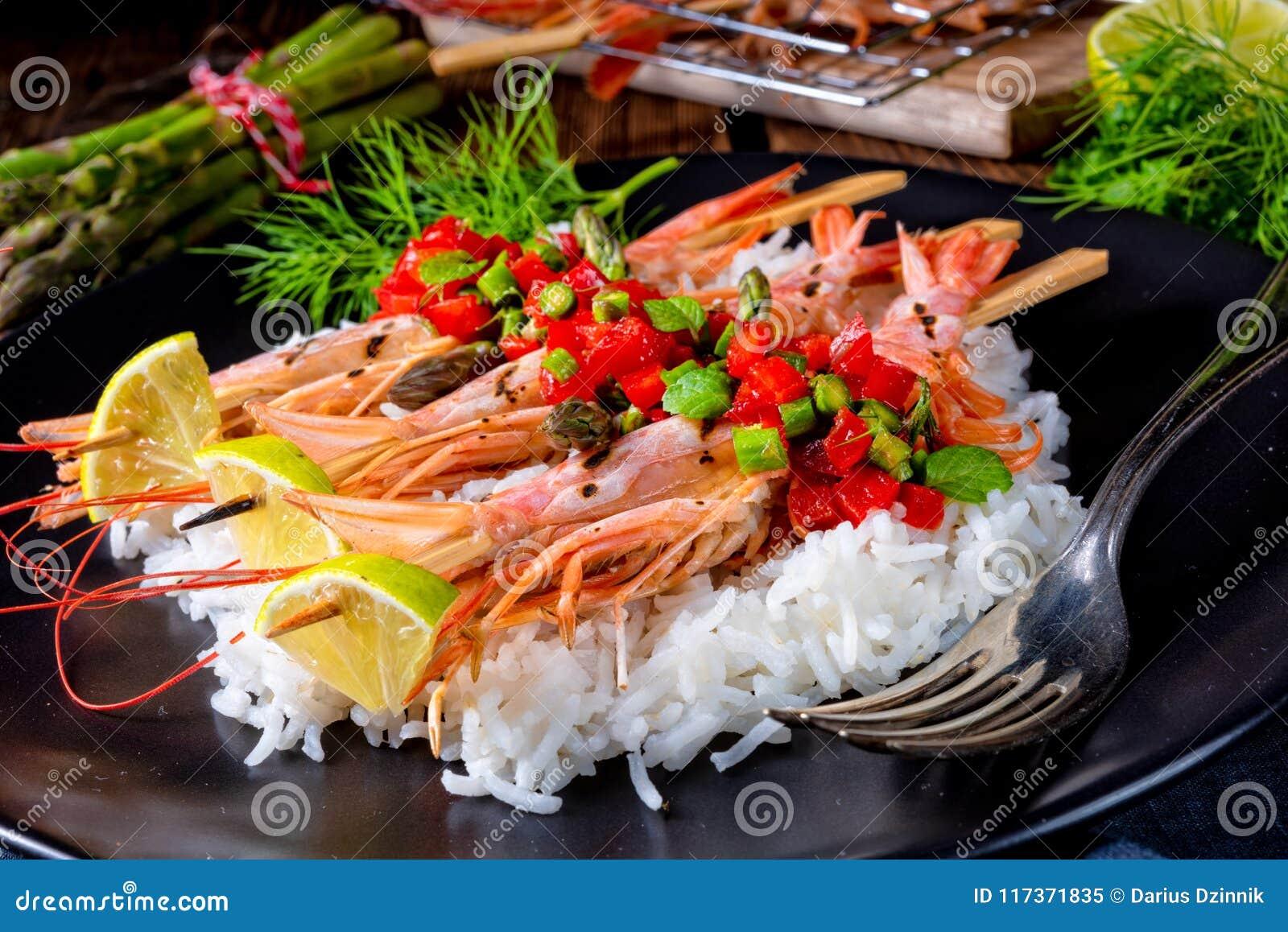 Ψημένες στη σχάρα κόκκινες αργεντινές γαρίδες με το κόκκινο salsa και το πράσινο σπαράγγι