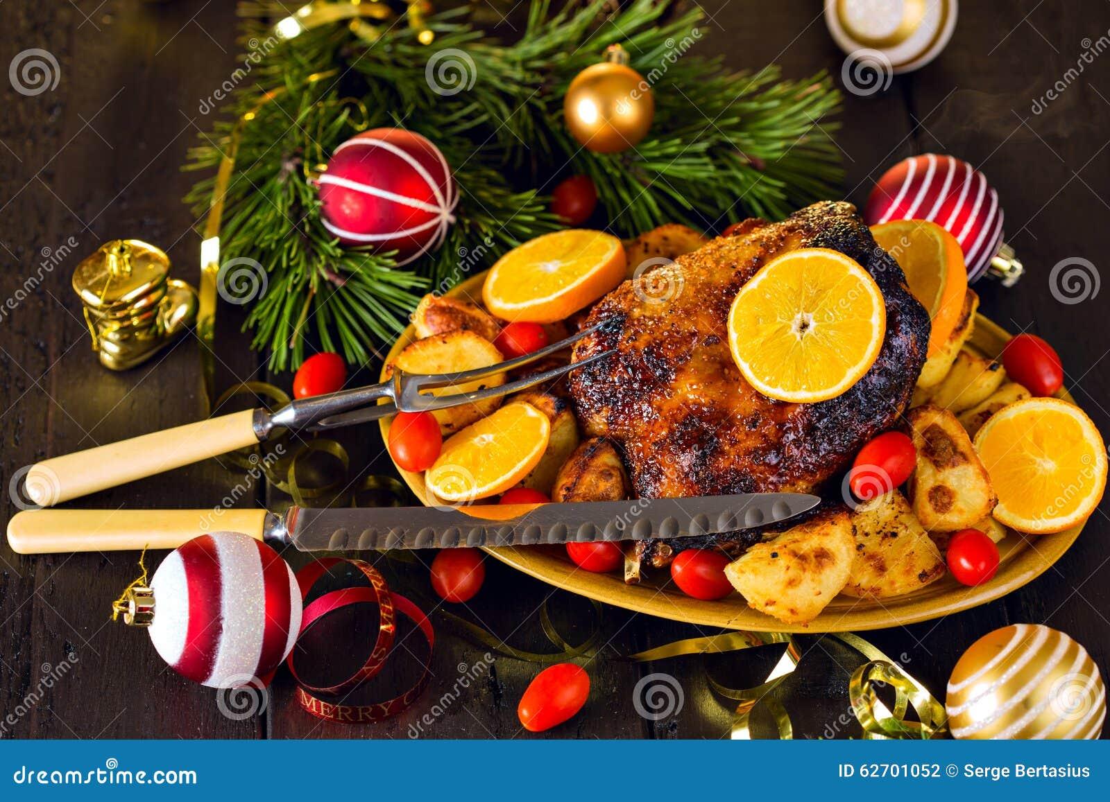 Ψημένη Χριστούγεννα πάπια που εξυπηρετείται με τις πατάτες, το πορτοκάλι και τις ντομάτες