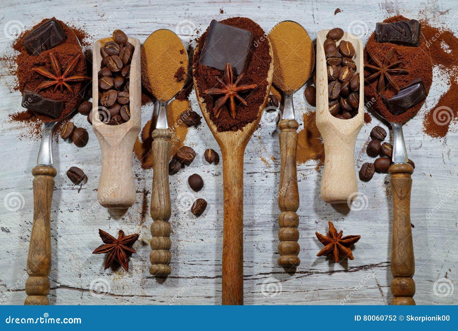 Ψημένος καφές, έδαφος, φασόλια και στιγμιαίος καφές στα εκλεκτής ποιότητας κουτάλια με την προσθήκη των κομματιών της σοκολάτας κ