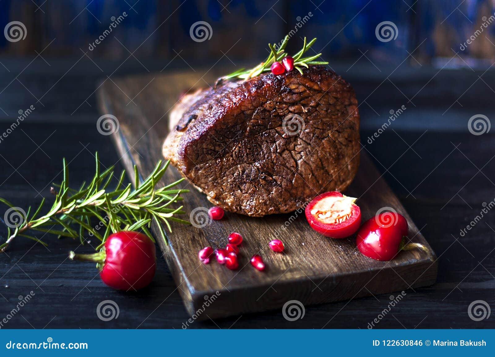 Ψημένο κρέας με το δεντρολίβανο και το κόκκινο πιπέρι Μπριζόλα beefburger γεύμα για τα άτομα Σκοτεινή φωτογραφία Μαύρη ανασκόπηση