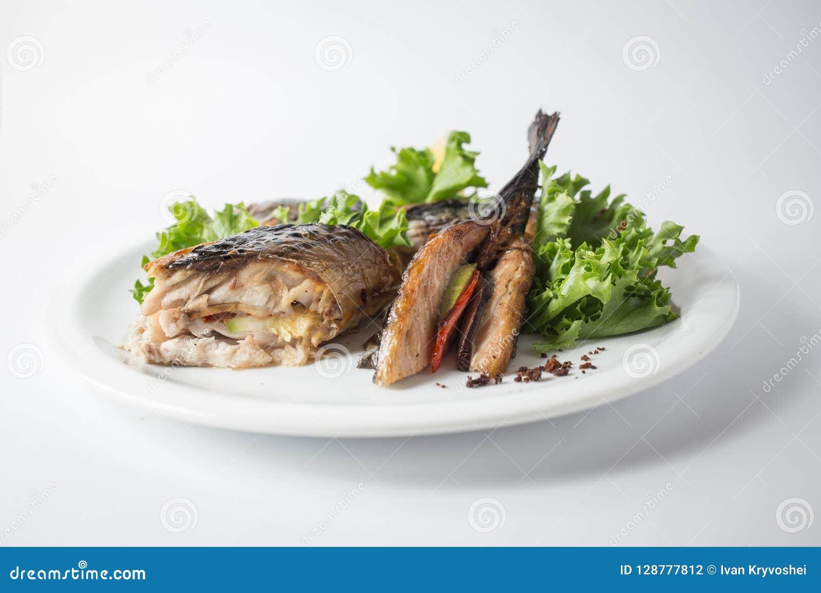 Ψημένο σκουμπρί με την πράσινη σαλάτα και λεμόνι στο άσπρο πιάτο