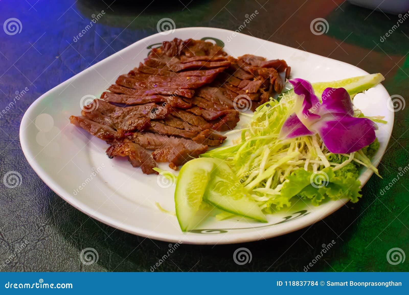 Ψημένο στη σχάρα βόειο κρέας σε ένα άσπρο πιάτο με τη σάλτσα και τα λαχανικά