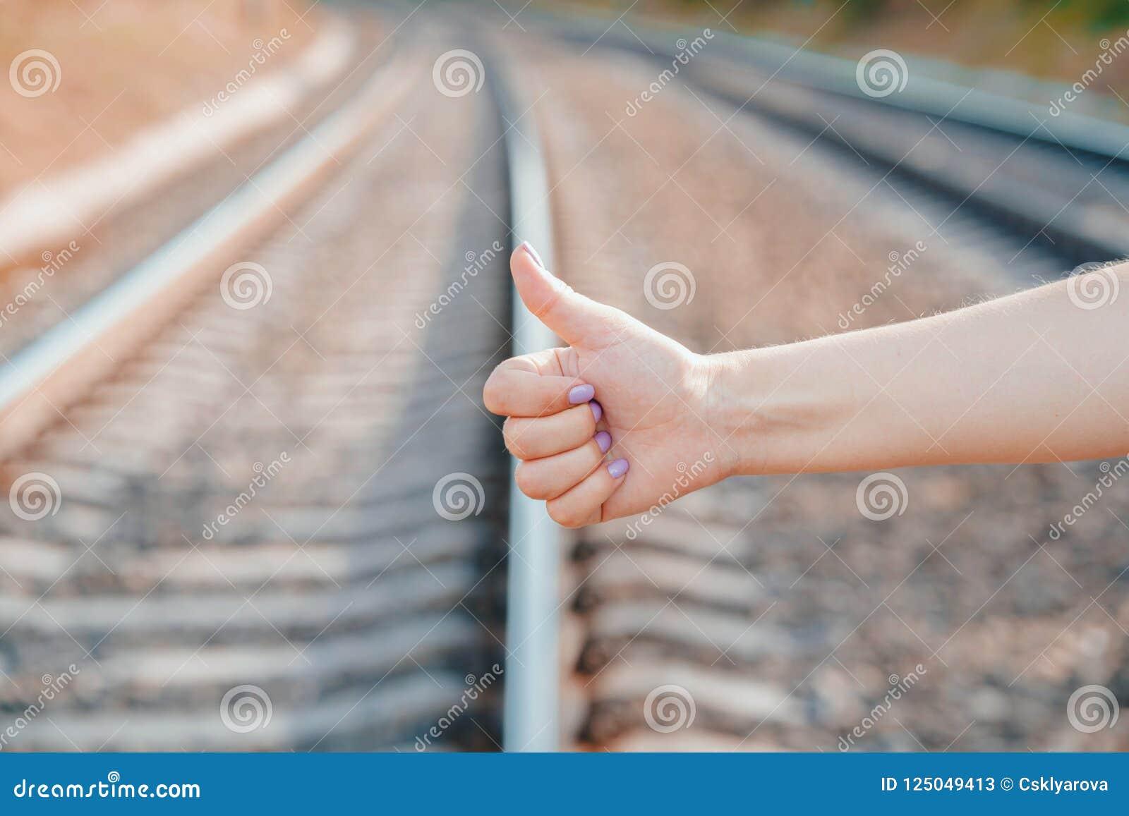 Ψηφοφορία για το δρόμο σιδηροδρόμων Κλείστε επάνω το θηλυκό χέρι με να κάνει ωτοστόπ τη χειρονομία
