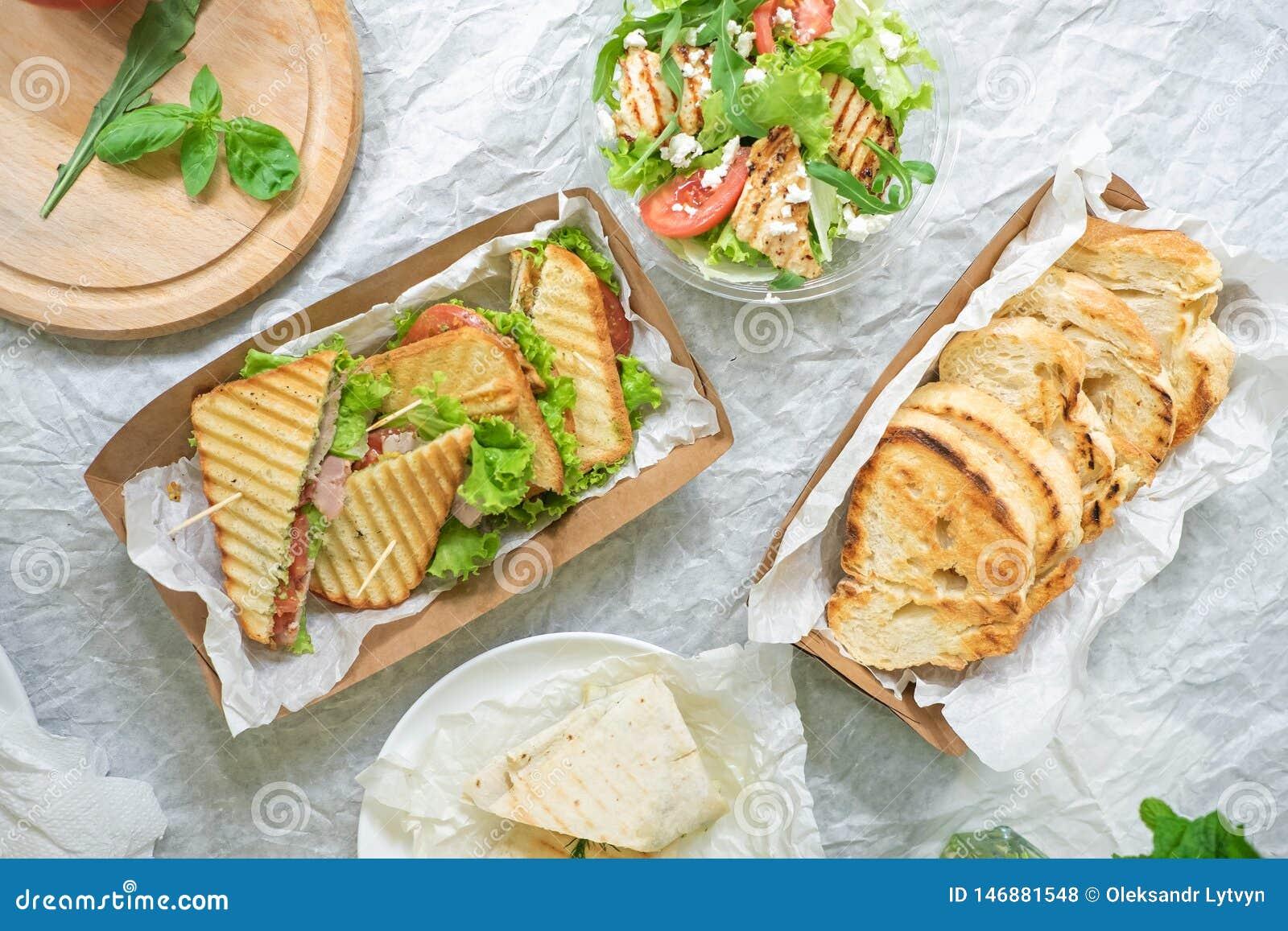 Ψωμί ζαμπόν με τη φυτική σαλάτα και ντομάτα σε έναν πίνακα και χαρτί