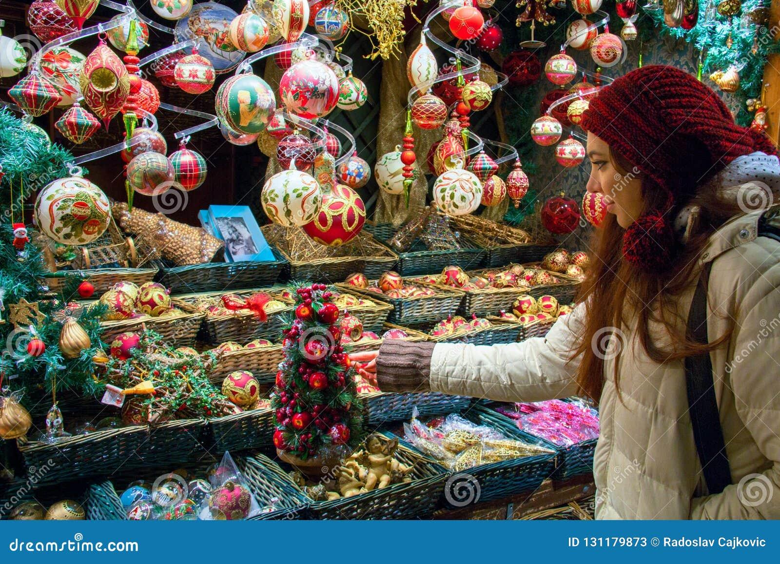 Ψωνίζοντας για τις διακοπές Χριστουγέννων, νέα γυναίκα στο παράθυρο επίδειξης αγοράς που επιλέγει τις διακοσμήσεις δέντρων