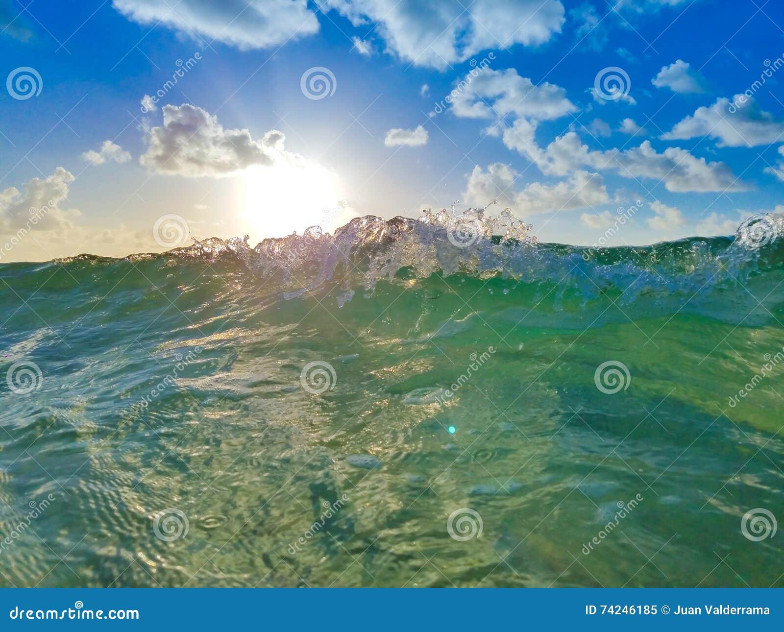 Ωκεάνιο κύμα με τον ήλιο, το μπλε ουρανό και τα σύννεφα