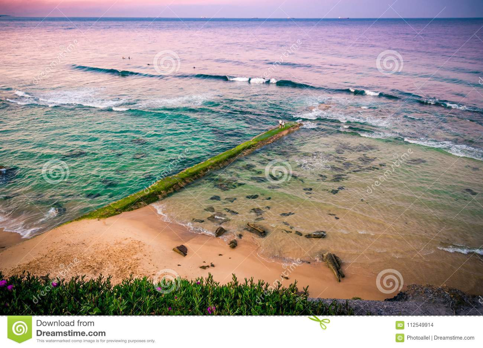 ωκεανός πέρα από την ανατολ Παλαιά αποβάθρα πετρών που εισβάλλεται με τα άλγη Αυστραλία, NSW, Νιουκάσλ