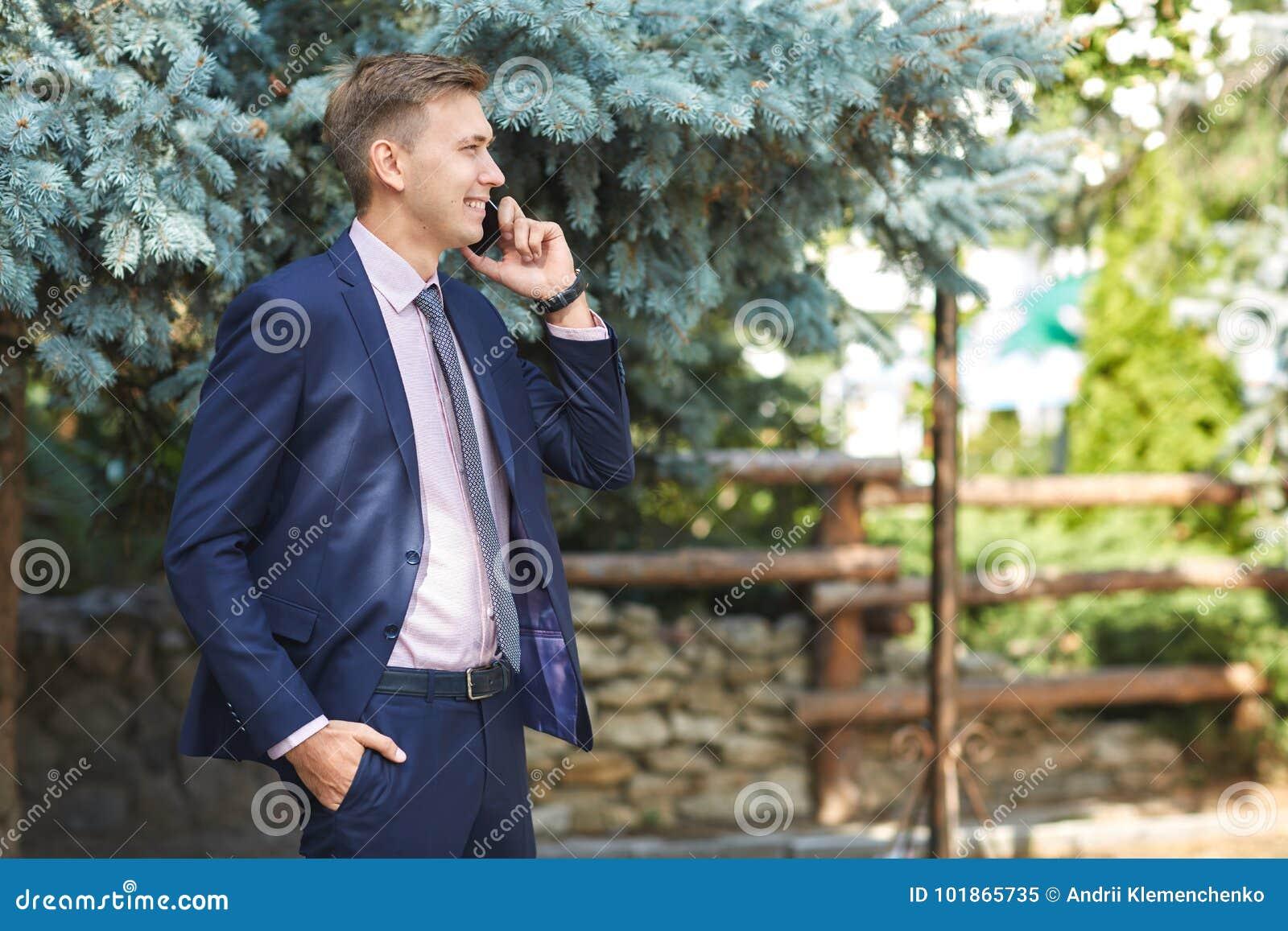 Ωραίος νεαρός άνδρας που εργάζεται στο πάρκο και που θέτει στη κάμερα χρυσή ιδιοκτησία βασικών πλήκτρων επιχειρησιακής έννοιας πο