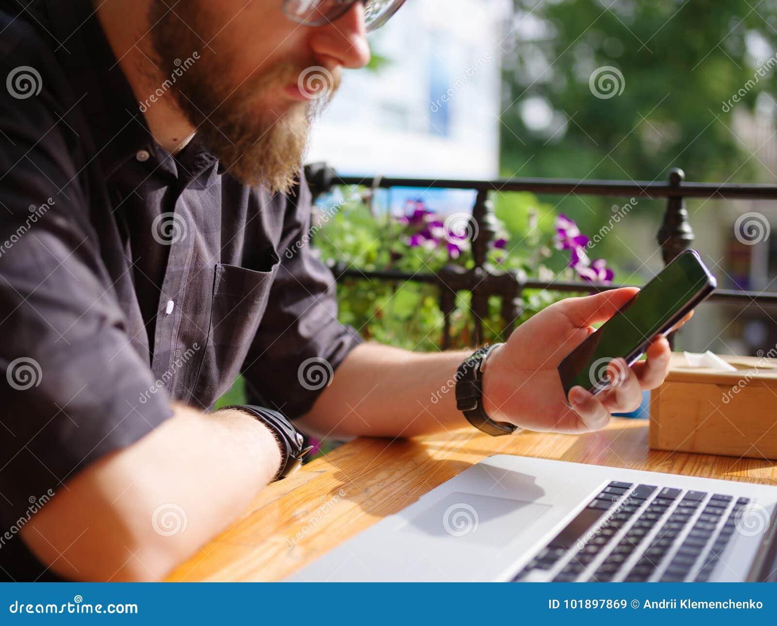 Ωραίος νεαρός άνδρας που εργάζεται στο lap-top καθμένος υπαίθρια χρυσή ιδιοκτησία βασικών πλήκτρων επιχειρησιακής έννοιας που φθά
