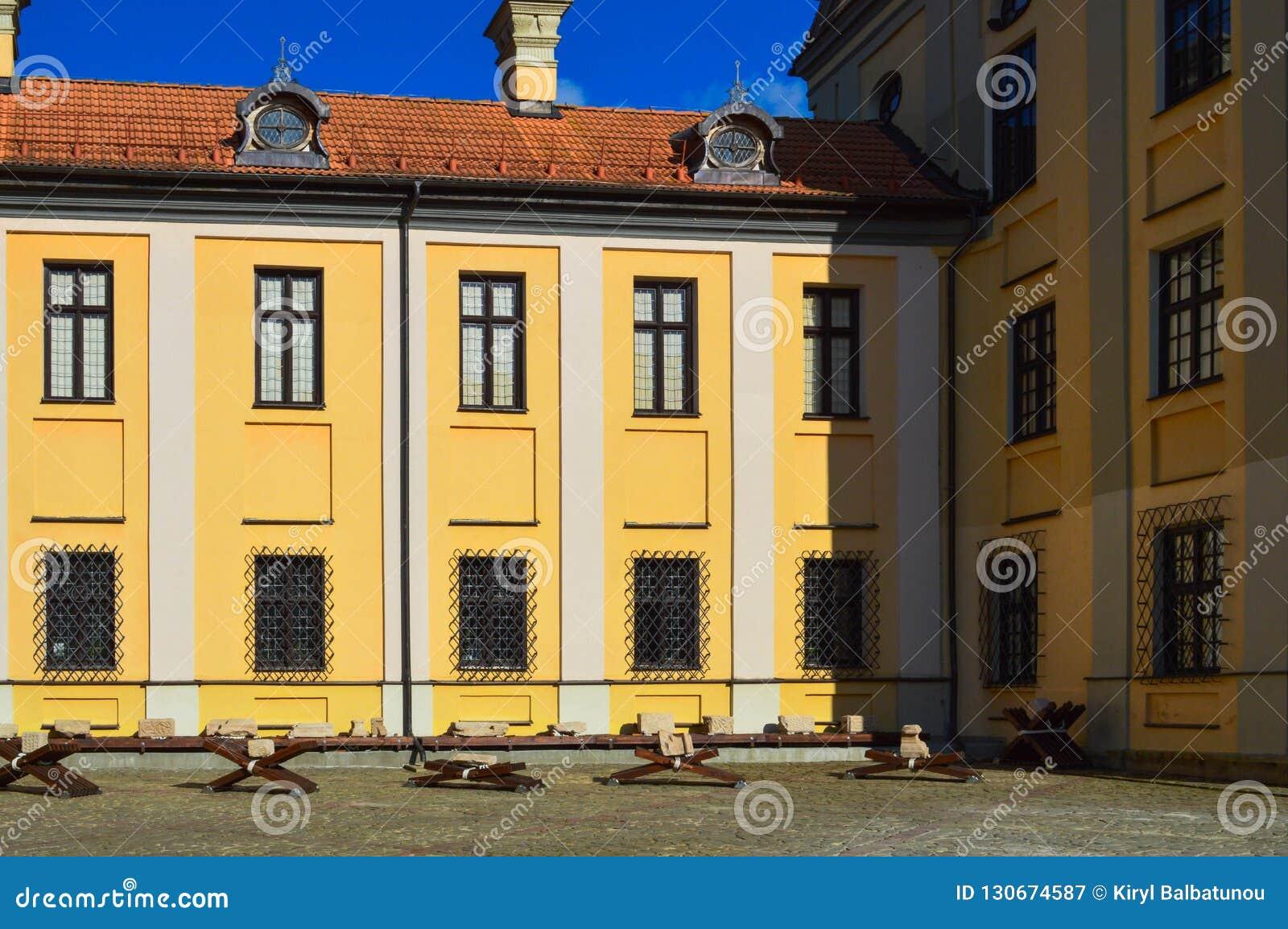 Όμορφα κίτρινα ιστορικά μεσαιωνικά ευρωπαϊκά κτήρια χαμηλός-ανόδου με ένα κόκκινο αέτωμα στεγών κεραμιδιών και ορθογώνια παράθυρα