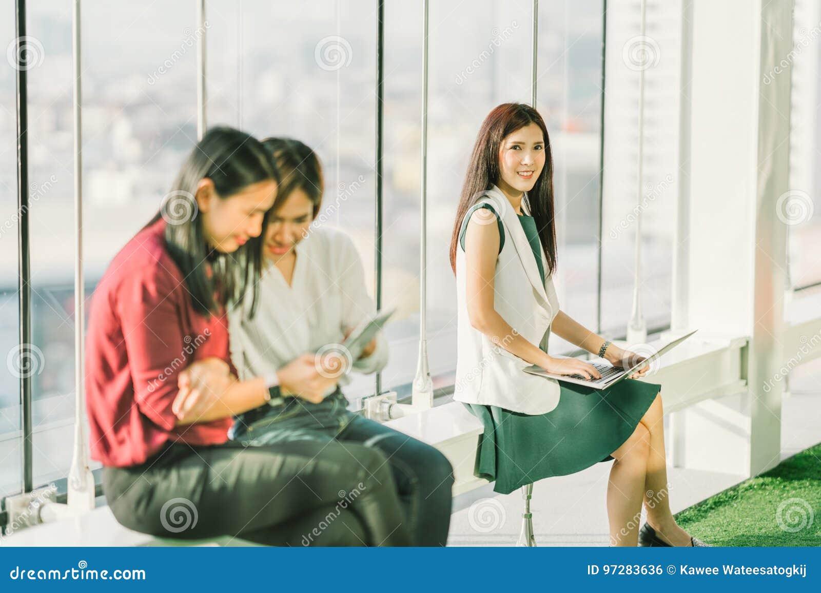 Όμορφα νέα ασιατικά κορίτσια που χρησιμοποιούν το σημειωματάριο lap-top και την ψηφιακή ταμπλέτα κατά τη διάρκεια του σπασίματος