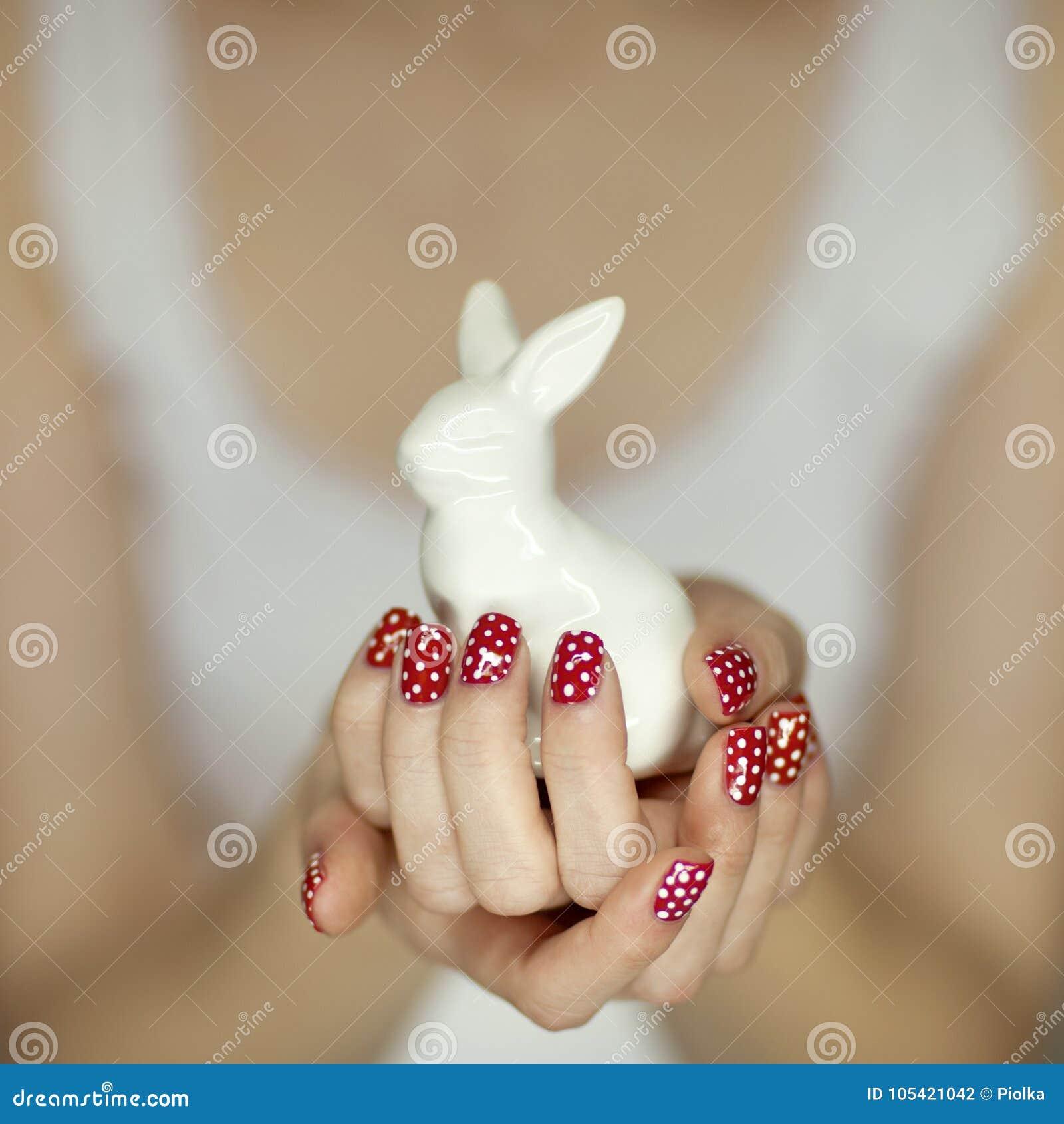 Όμορφα χέρια γυναικών με το κόκκινο λαγουδάκι Πάσχας εκμετάλλευσης τέχνης στιλβωτικής ουσίας καρφιών