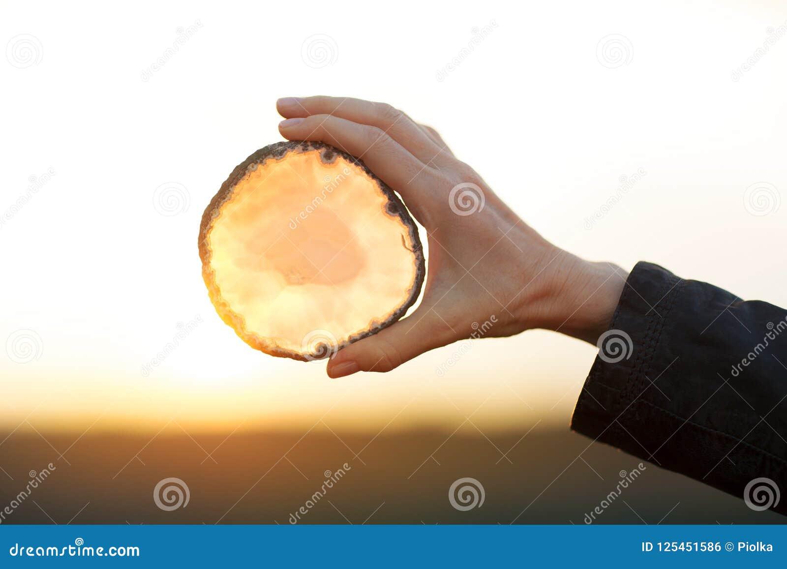 Όμορφα χέρια γυναικών που κρατούν το κρύσταλλο φετών αχατών στο φως του ήλιου