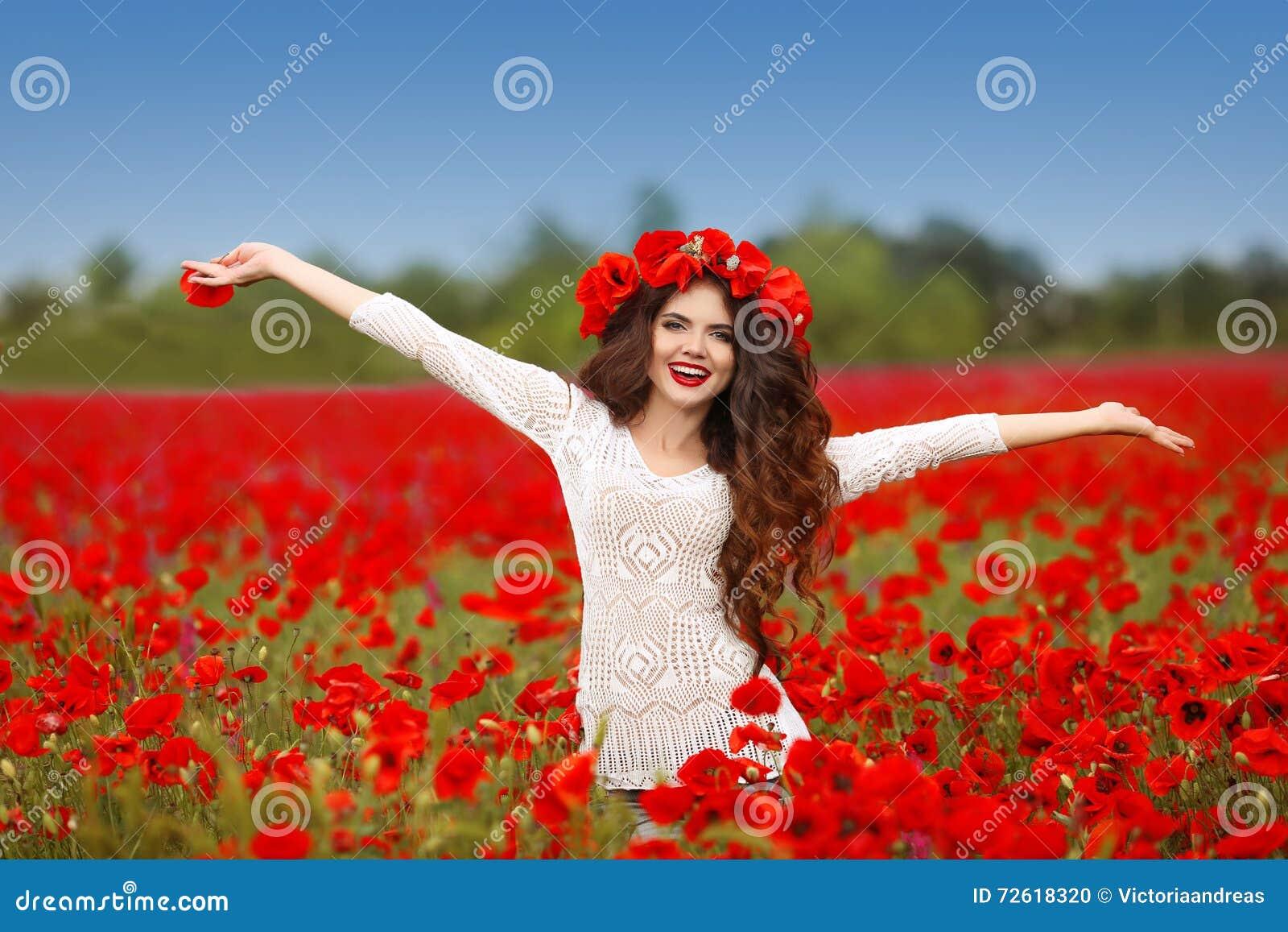 Όμορφες ευτυχείς ανοικτές αγκάλες γυναικών χαμόγελου στον κόκκινο τομέα παπαρουνών natur