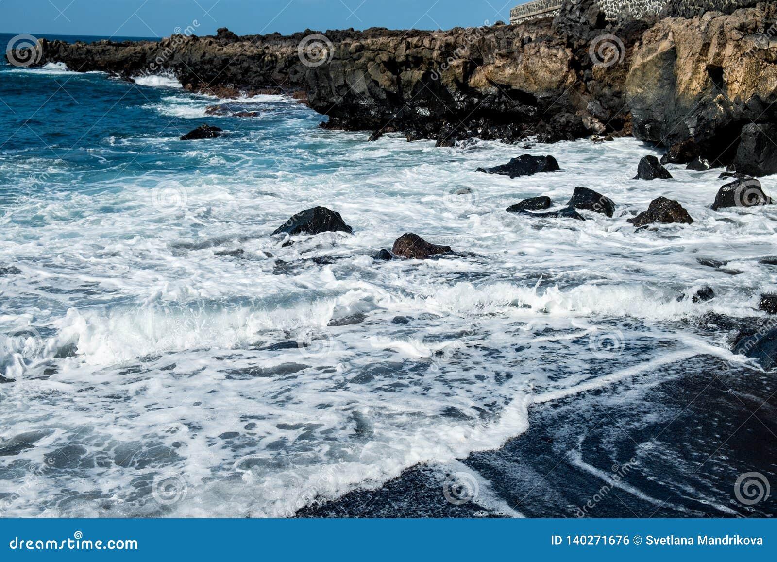 Όμορφη άποψη σχετικά με το ωκεάνιο νερό και τη μαύρη άμμο λάβας