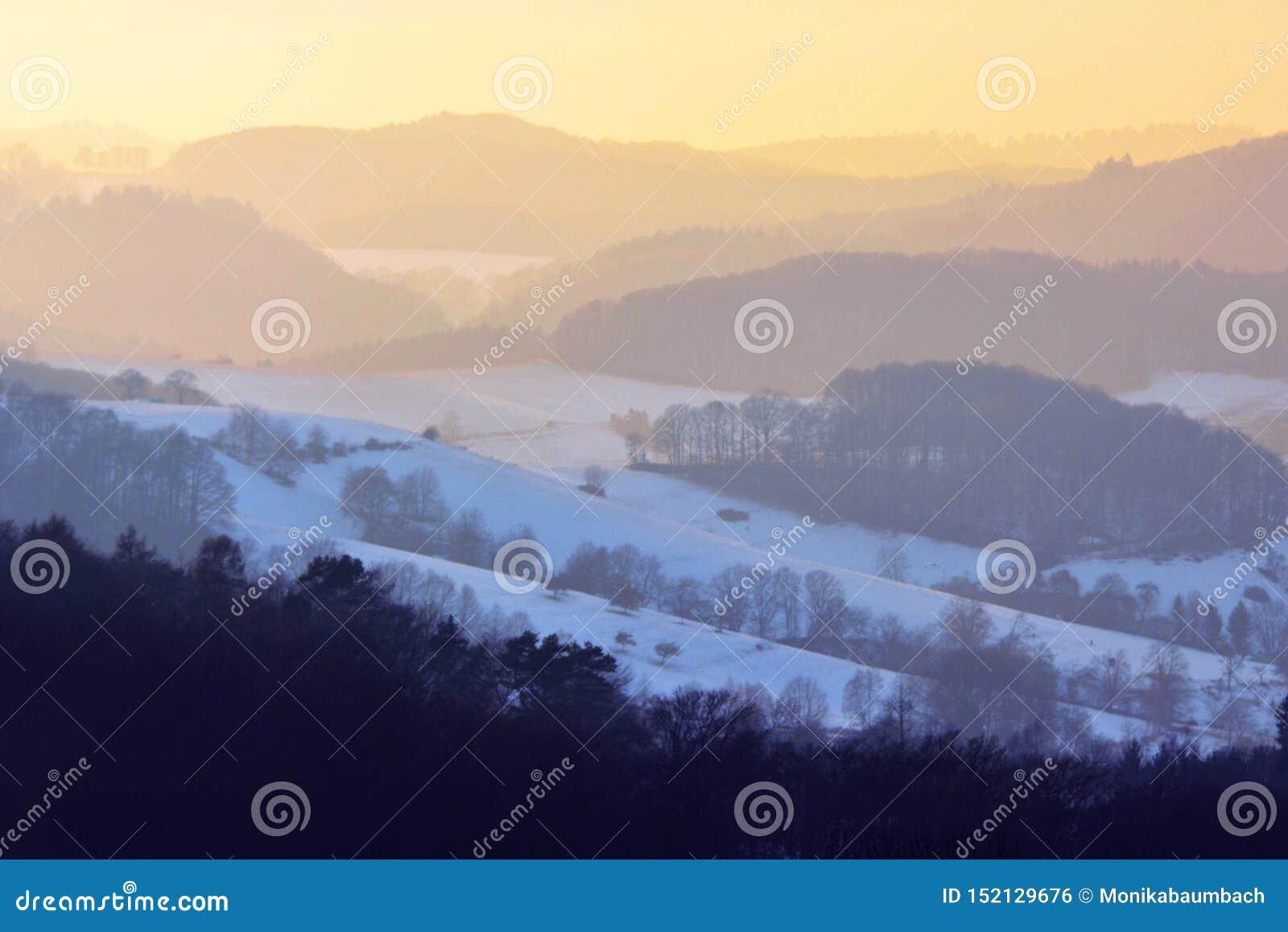 Όμορφη άποψη τοπίων πέρα από το δάσος Odenwald με το χιόνι στο ηλιοβασίλεμα το χειμώνα στη Γερμανία