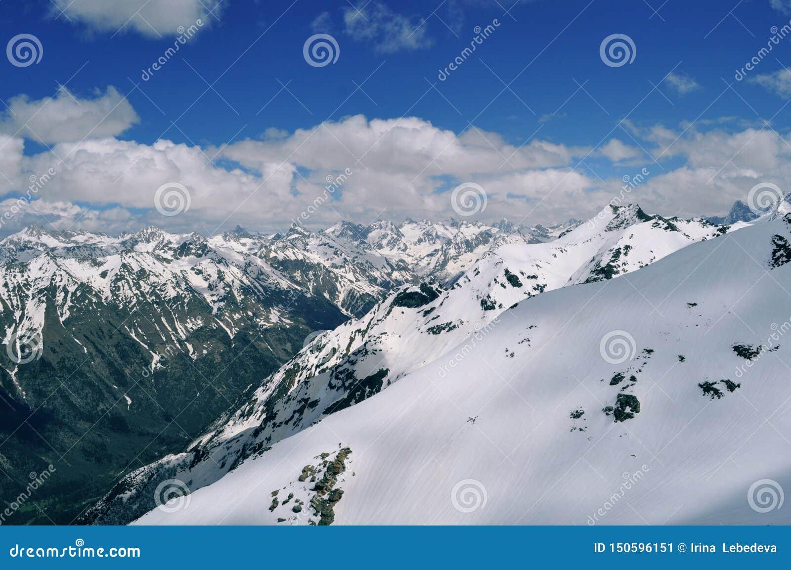 Όμορφη άποψη του τοπίου βουνών: σειρές βουνών, άσπρα σύννεφα