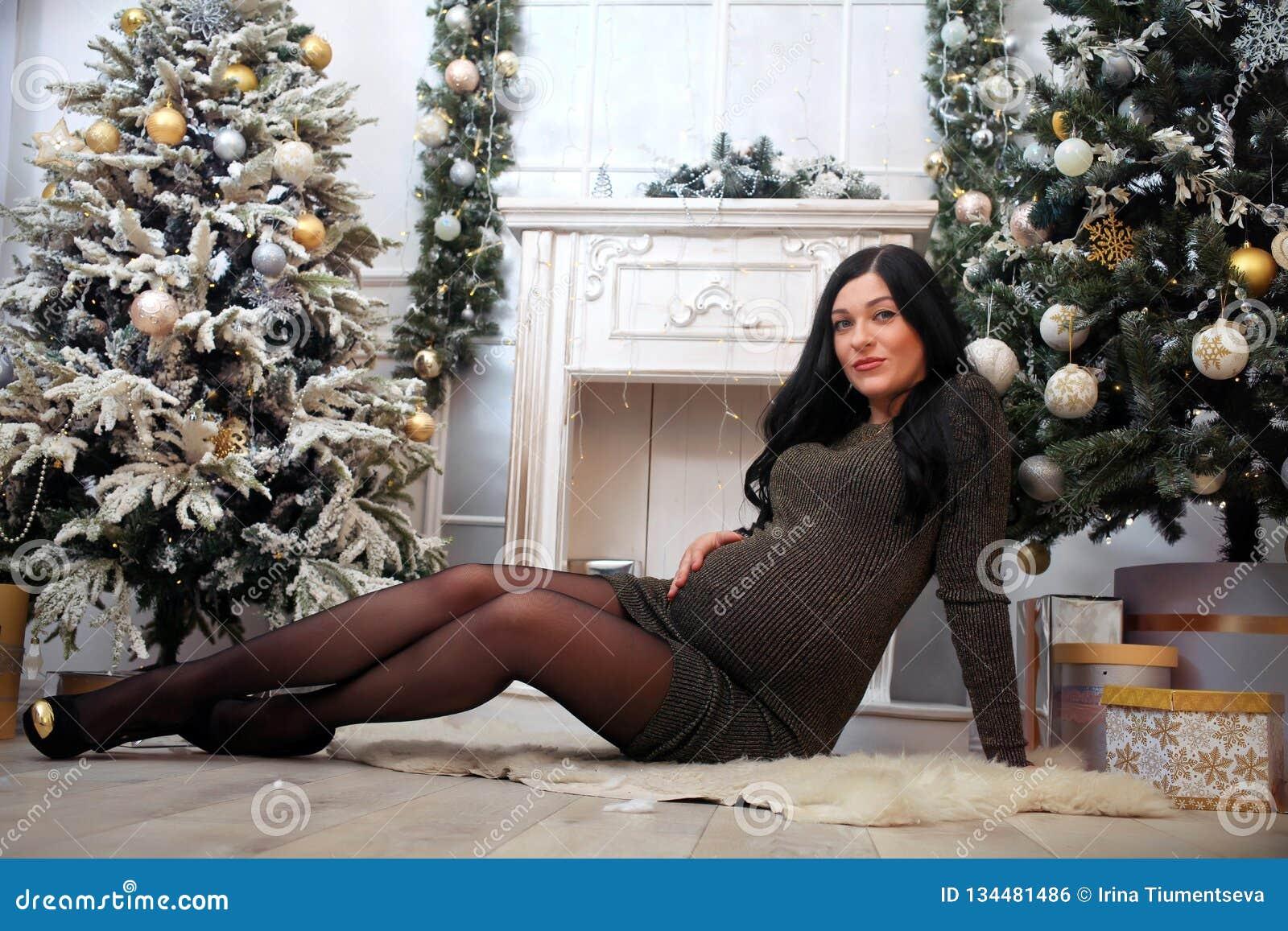 Όμορφη έγκυος γυναίκα σε ένα φόρεμα διακοπών