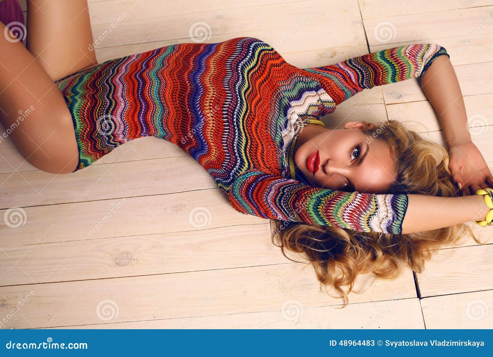 Όμορφη αισθησιακή γυναίκα με την ξανθή σγουρή τρίχα στο ζωηρόχρωμο κοστούμι