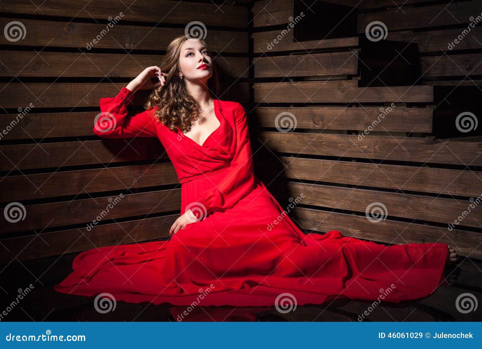 6d1155abd801 Πορτρέτο της όμορφης αισθησιακής γυναίκας στη μακροχρόνια συνεδρίαση  φορεμάτων μόδας κόκκινη στο πάτωμα πέρα από το ξύλινο υπόβαθρο