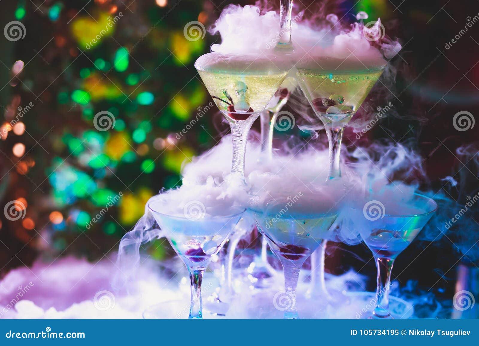 Όμορφη γραμμή πυραμίδων διαφορετικών χρωματισμένων κοκτέιλ οινοπνεύματος με τη μέντα στη γιορτή Χριστουγέννων, το tequila, martin