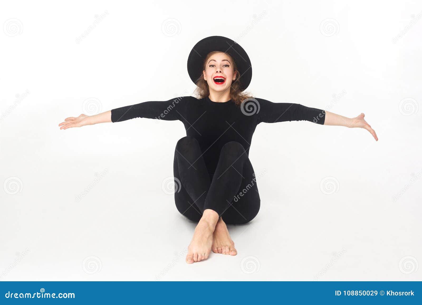 Όμορφη γυναίκα ευτυχίας στο καπέλο, που κάθεται στο πάτωμα