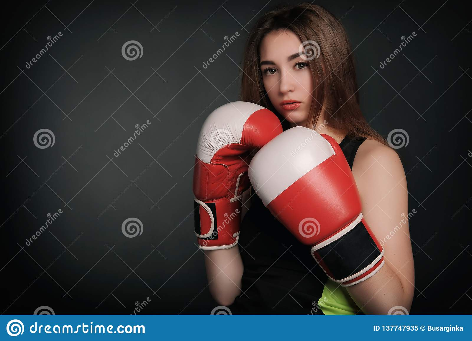Όμορφη γυναίκα με τα κόκκινα εγκιβωτίζοντας γάντια, μαύρο υπόβαθρο