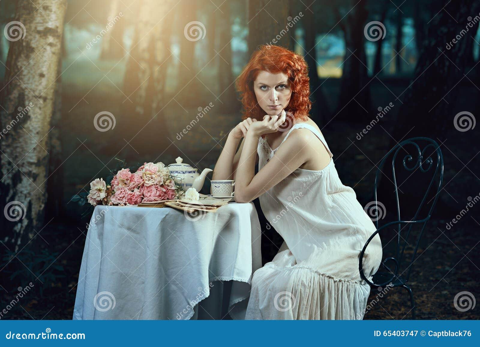 Όμορφη γυναίκα με την κόκκινη τρίχα στο ρομαντικό δάσος