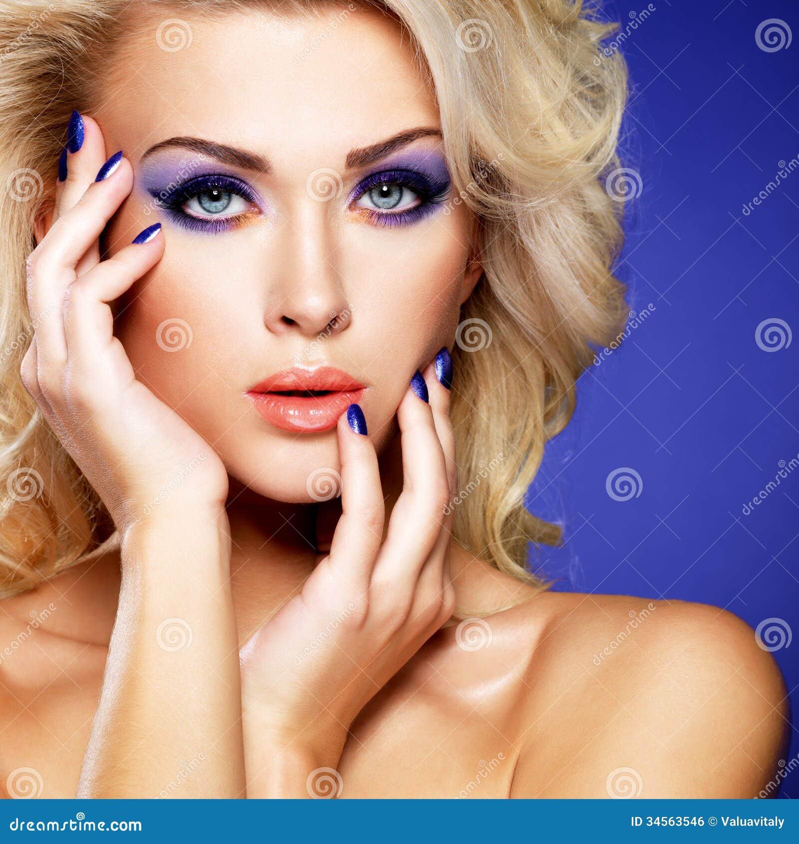 Όμορφη γυναίκα με το πορφυρό μανικιούρ ομορφιάς και makeup των ματιών.