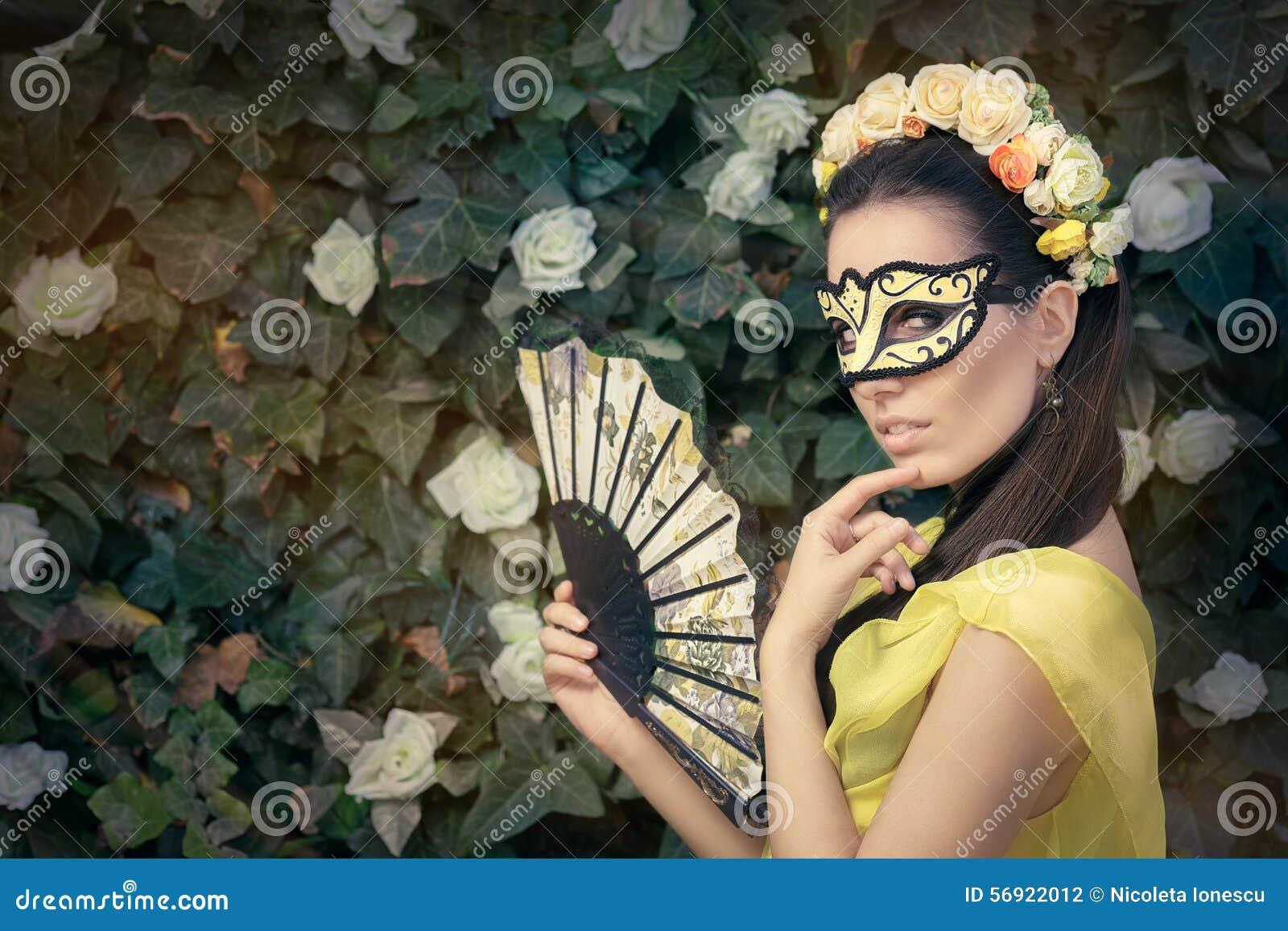 Όμορφη γυναίκα με το Floral στεφάνι, τη μάσκα και τον ανεμιστήρα