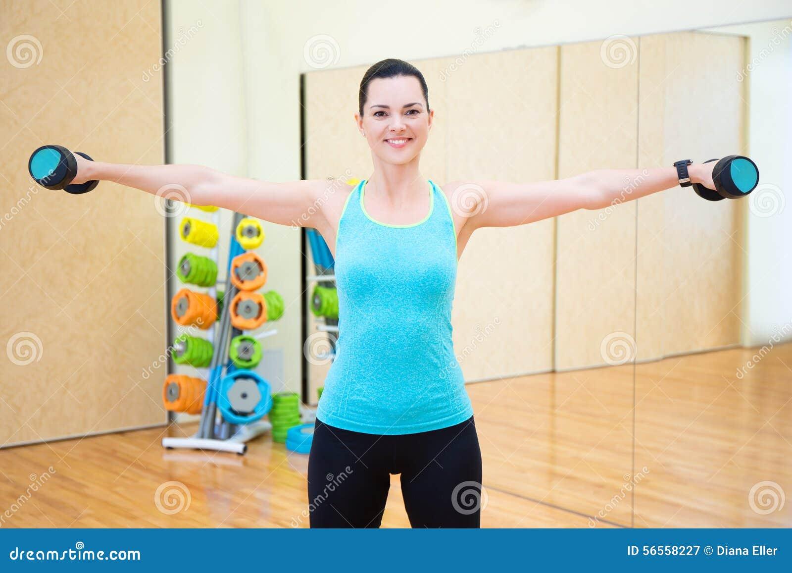 Download Όμορφη γυναίκα που ασκεί με τους αλτήρες στη γυμναστική Στοκ Εικόνα - εικόνα από αρκετά, χαμόγελο: 56558227