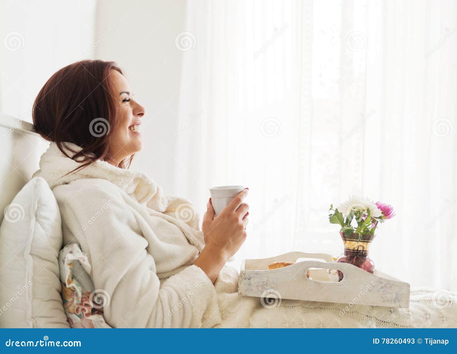 Όμορφη γυναίκα που βάζει και που απολαμβάνει το πρόγευμα στο κρεβάτι