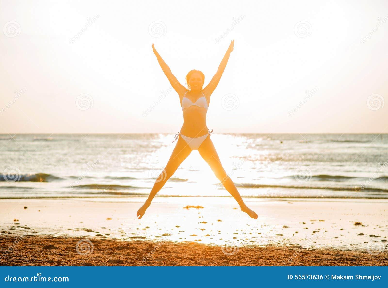 Download Όμορφη γυναίκα που στέκεται μπροστά από το ηλιοβασίλεμα στην παραλία Στοκ Εικόνες - εικόνα από ευτυχία, καλοκαίρι: 56573636