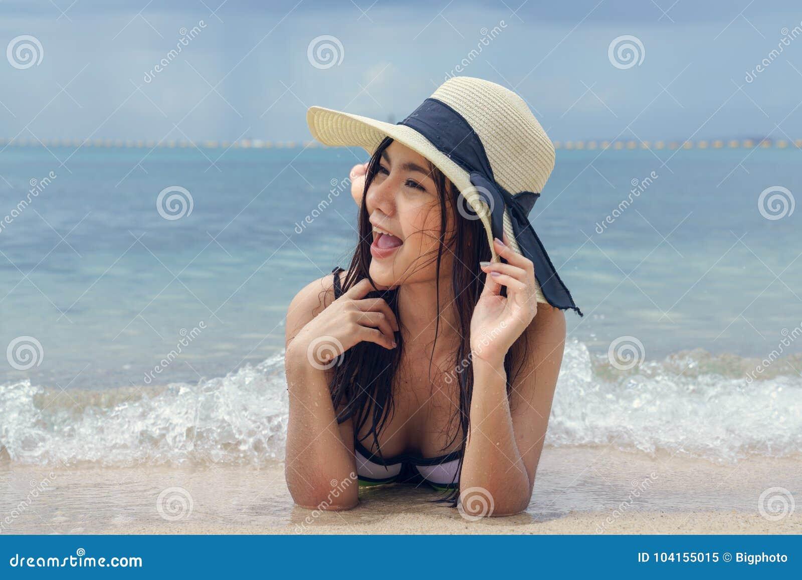 Όμορφη γυναίκα που φορά ένα καπέλο που βρίσκεται στην παραλία