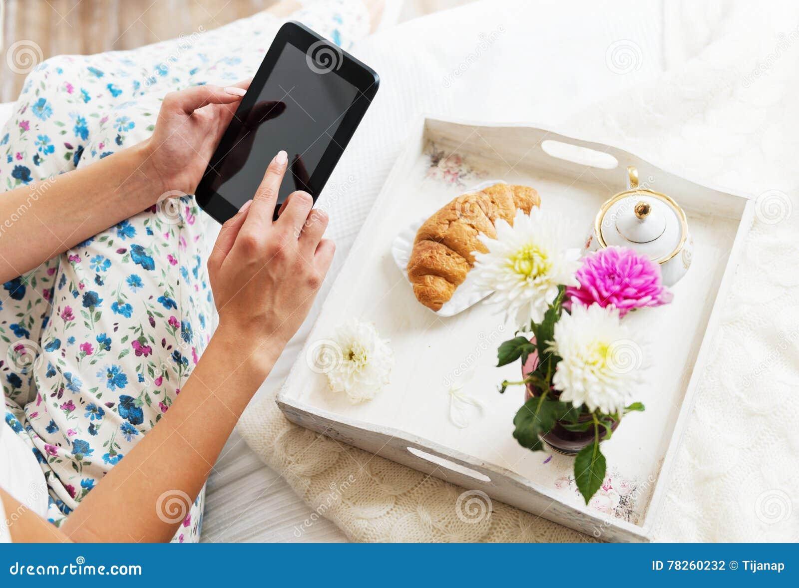 Όμορφη γυναίκα που χρησιμοποιεί μια ταμπλέτα με το πρόγευμα στο κρεβάτι