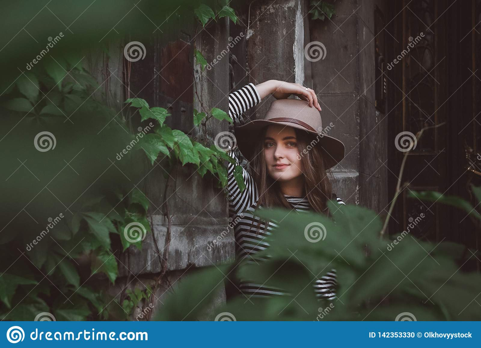 Όμορφη γυναίκα σε ένα ριγωτό πουκάμισο που κρατά το καπέλο της και που εξετάζει μια κάμερα