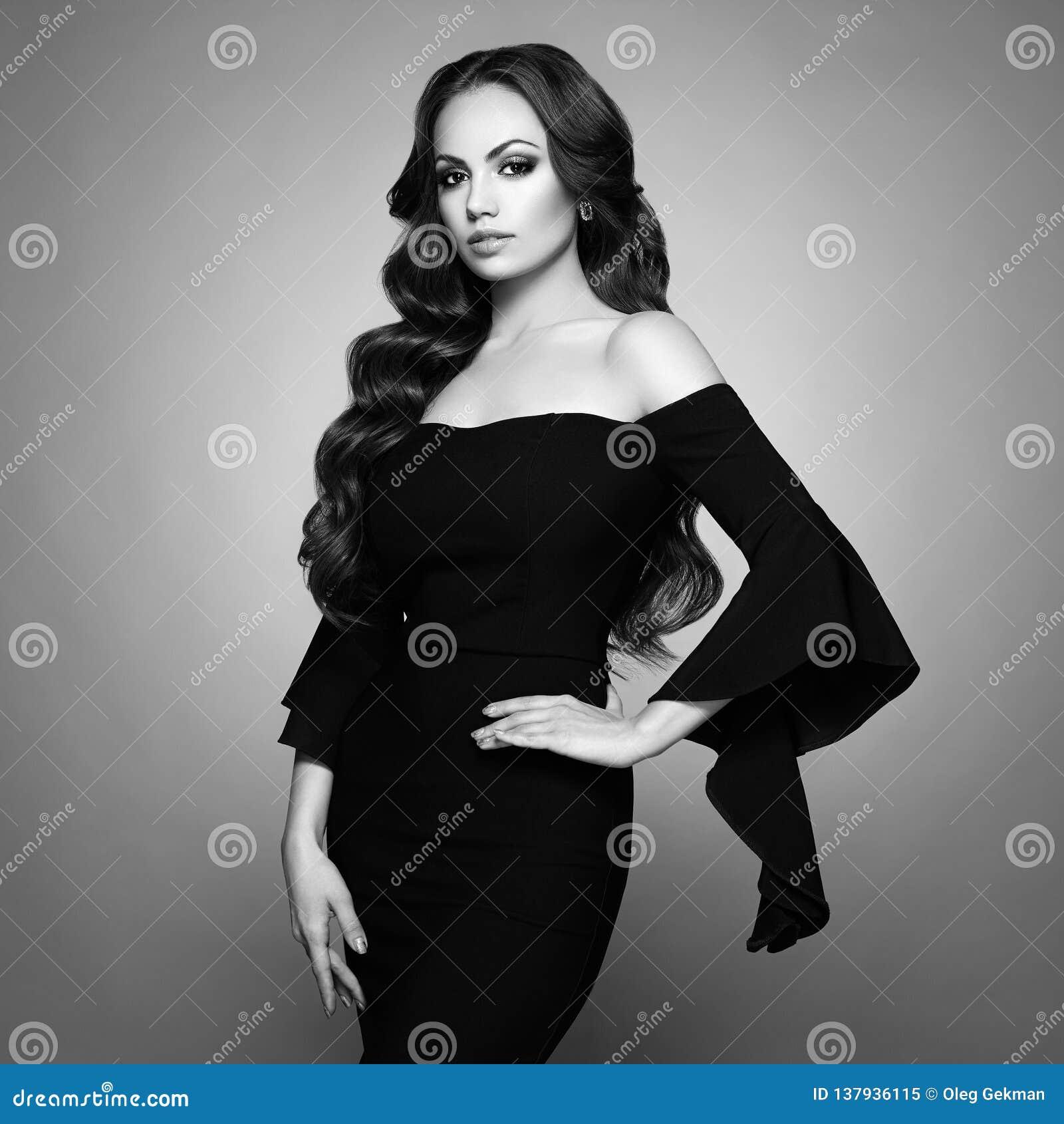 Όμορφη γυναίκα στο κομψό μαύρο φόρεμα βραδιού