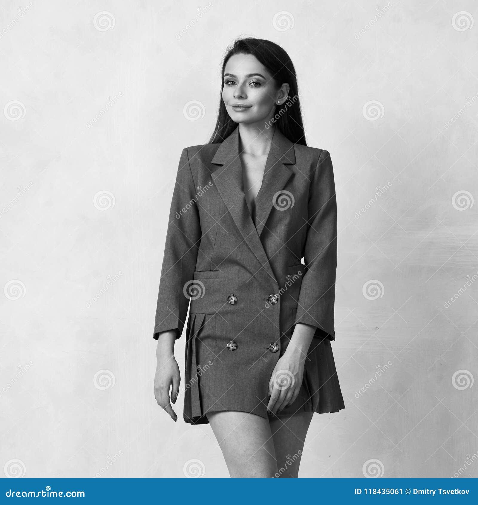 Αρκετά θηλυκό πρότυπο που φορά το γκρίζο μίνι φόρεμα σακακιών με τέσσερα  κουμπιά και τα βαλμένα τακούνια παπούτσια που θέτουν στο στούντιο Όμορφη  γυναίκα ... 2ac175fc73e