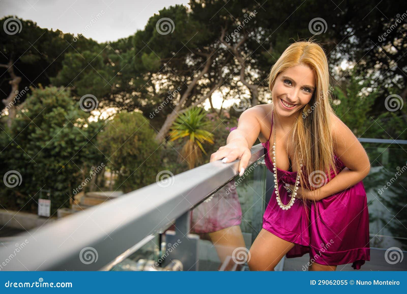 c6f52d840e5f Όμορφη προκλητική ξανθή γυναίκα στο μπαλκόνι στο ηλιοβασίλεμα. Περισσότερες  παρόμοιες στοκ εικόνες